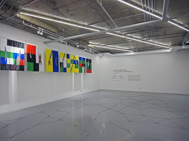 Colourful, geometric flags by Boedi Widjaja hang along a wall in a white gallery space.