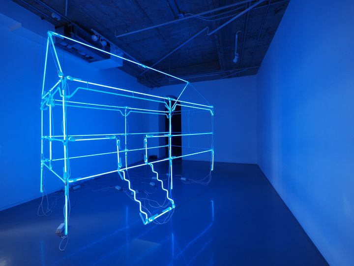 A neon sculpture with Vuth Lyno radiates blue in a gallery room.