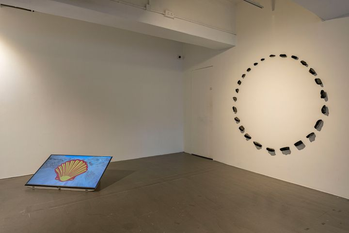 A video screen on the floor features the Shell logo, and is accompanied by a sculptural installation on the wall to the right that features a circle of asphalt shards.