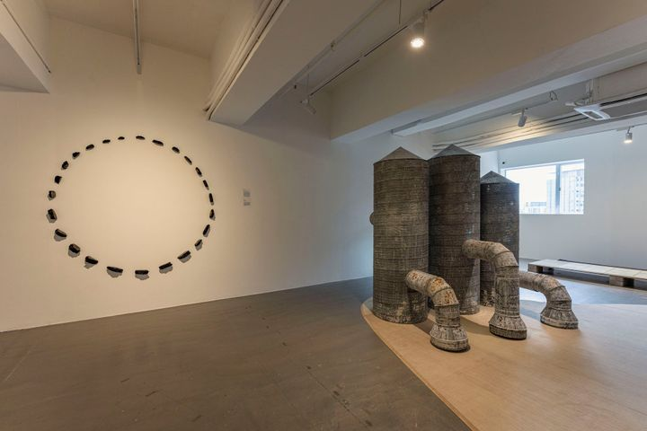 A circle of asphalt shards is mounted on the wall alongside three replicas of metal silo towers.