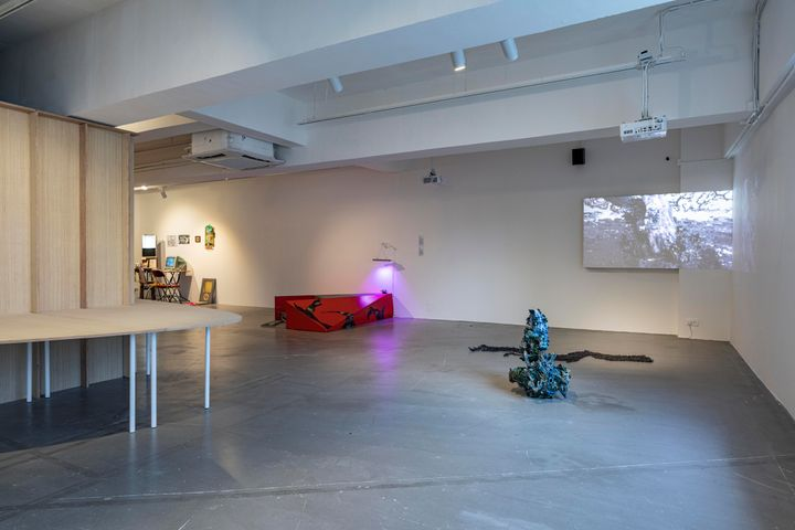 A room full of sculptures and installations, including a wooden structure to the left, a small red podium to the right, as well as a clay sculpture of tangled, serpentine forms.