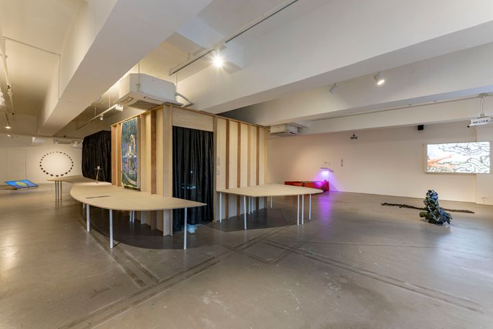 A wooden structure featuring openings covered by black blinds is surrounded by sculptures hanging on the walls and on the floor of a white exhibition space.