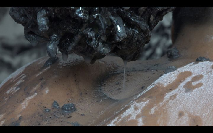 The back of a muddied human figure is encrusted with dried dirt, with a clump of mud with water streaming from it hanging between their shoulder blades.