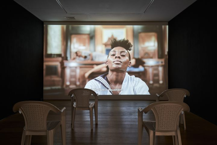 A large screen in a darkened gallery space features a woman in a sailor top, dancing.