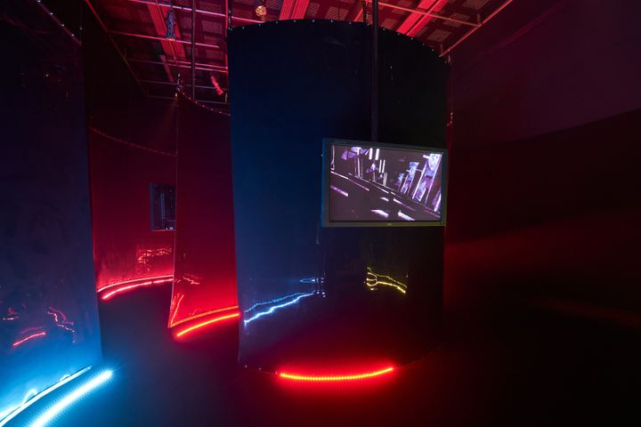 A dark room features rows of black sheets that are lit from below with neon tubing and feature a screen.