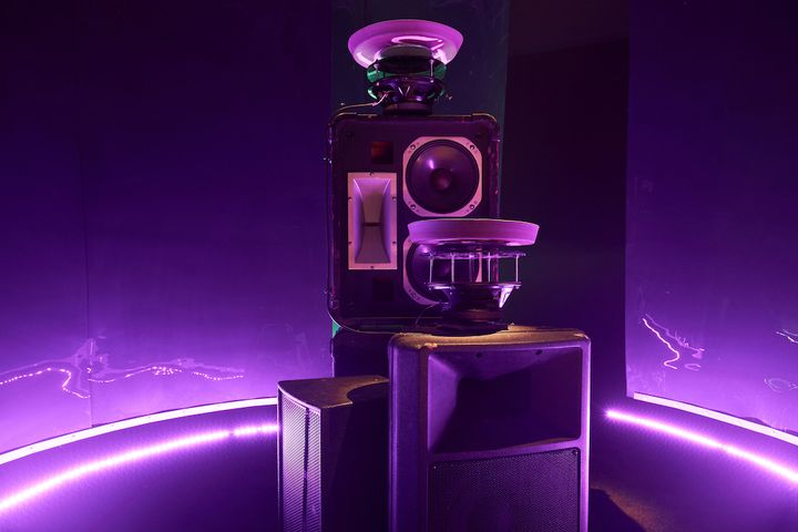 A sound system sits in a purple-hued gallery space with trays placed on top of it to form a sonic art installation.