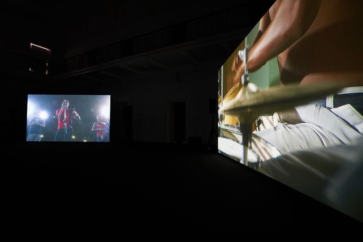Two large screens in a darkened exhibition space show musicians playing. The right screen shows a close up of a purcussionist's hand, while the right-hand screen pictures a singer.