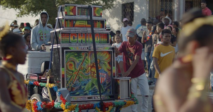 A colourful sound system is at the centre of the image, surrounded by people partying in the street.