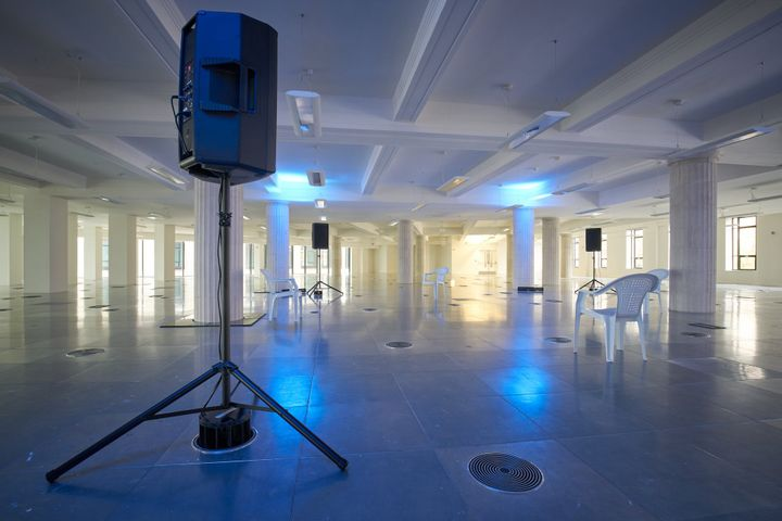 An empty room features a circle of chairs and stage monitors that form a sonic art installation in a dimly lit room.