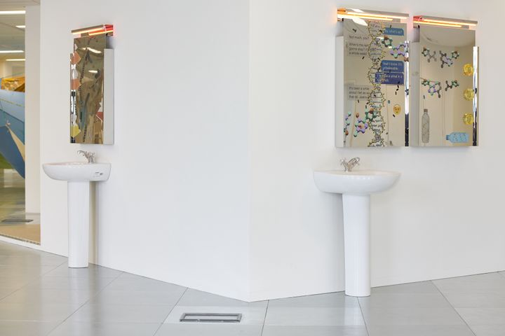 Two sinks with mirrors above them form an art installation in the gallery space.