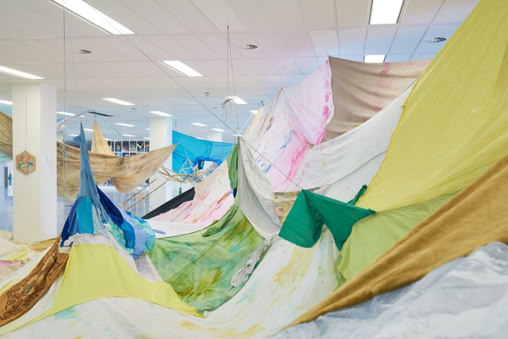 Sheets of colourful fabric hanging from the ceiling in a gallery space to form an art installation.