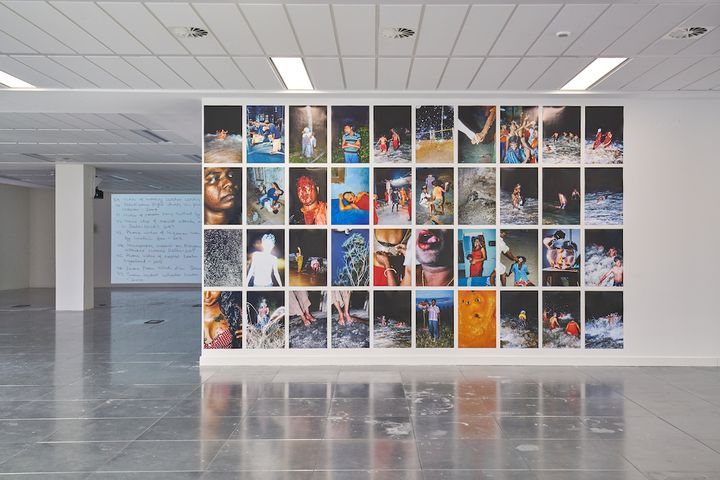 A mural of four rows of images, with ten on each row, features night-time shots of people at the beach.