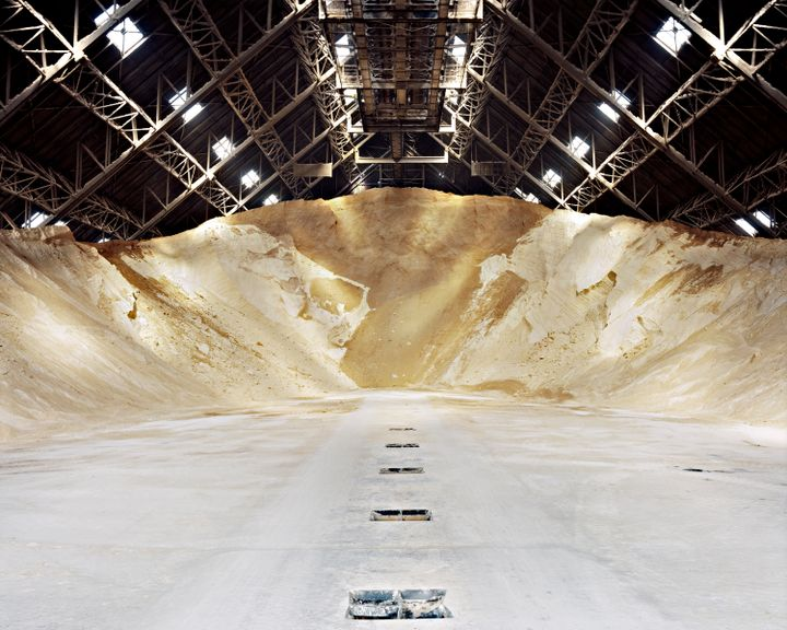 A photograph featuring a pile of sugar in an industrial warehouse space.