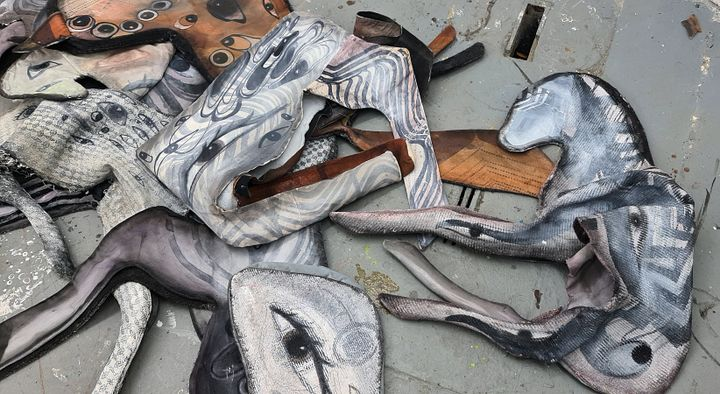 Various textile cuttings in all shapes, sizes and textures scattered on a grey floor