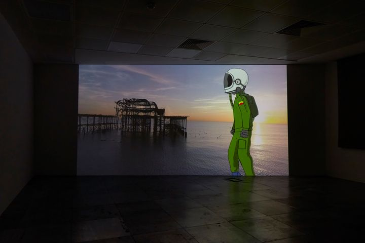 A big screen in a dark room showing an illustration of a man in a green spacesuit with white space helmet, against an image of a wharf structure at sea, a video still of Larry Achiampong's work