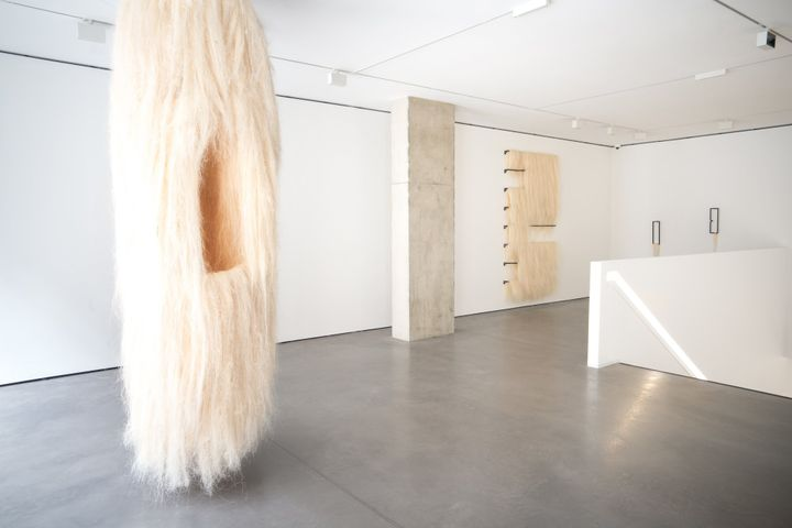 Artist Kapwani Kiwanga's fluffy cream-coloured furry sculpture hangs from the ceiling, while on the background another cream-coloured furry sculpture hangs against a white wall
