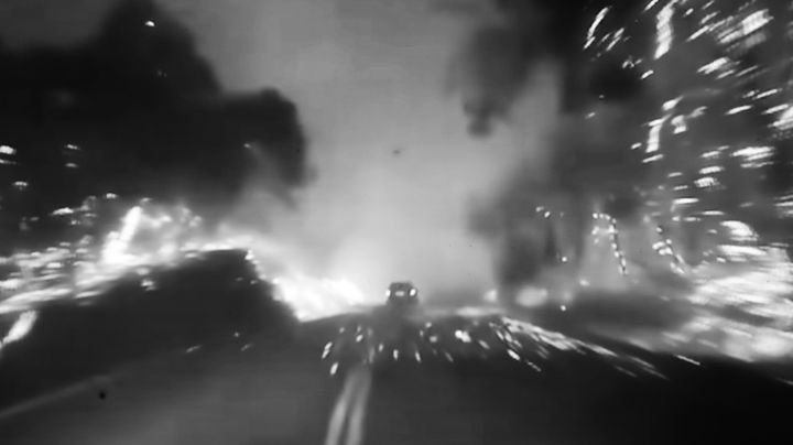 A blurred black and white film still features a car driving through what resembles a blazing forest.