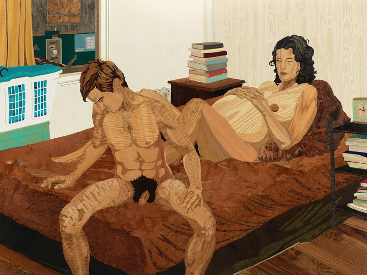 A pregnant woman and a man both recline naked on a bed in a city apartment.