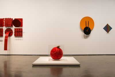 Colourful sculptures by Lygia Pape line the walls of the exhibition space, shaped in geometric forms such as diamonds, squares, and circles. A red sphere is placed on top of a low pedestal in fromt of them.