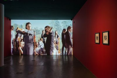 A large video installation by Olivia Plender features two women with a crowd behind them pointing wooden guns towards the camera. The film is shown in a darkened room, flanked by a deep-red wall.