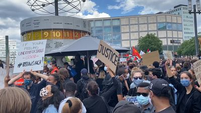 Crowds assembled in Berlin for a Black Lives Matter protest are wearing masks and holding up signs, two of which read 'Justice' and 'If You're Feeling Uncomfortable - Good'.