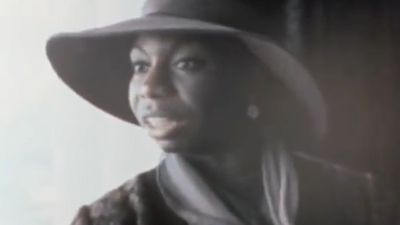 In a slightly blurred video capture, Nina Simone is captured mid-discussion in a broad-rimmed hat.