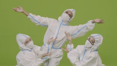 Three performers in protective suits are dancing in synchronisation, with only their eyes visible.
