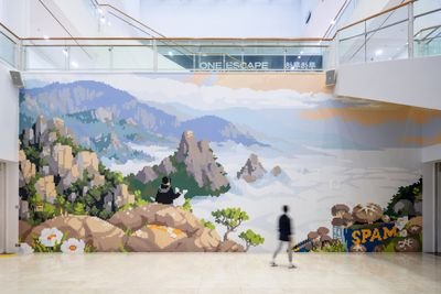 A pixellated landscape image is spread across a wall, depicting the top of a mountain overlooking cloud cover. A figure is captured from behind, sitting and looking at the view alongside a white rabbit or dog.