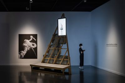 A darkened exhibition space contains a triangular wooden scaffold and a portrait-format screen to the left, showing a white cloud against a black background.