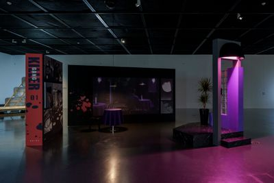 The interior of an empty bar is replicated with free-standing walls that have a pink glow projected on them.