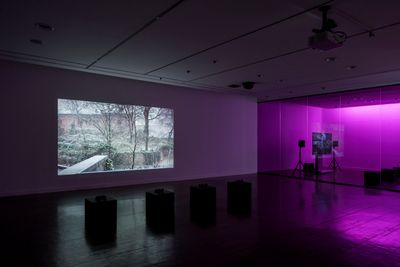 A photograph of a grey, snow dusted exterior is projected onto a wall in a darkened exhibition space where a pink glow emits from the far right of the room.