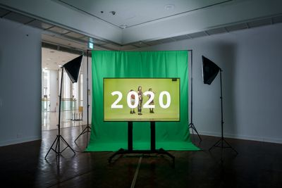 Green fabric hangs from the ceiling in a darkened exhibition space, with two studio lights either side of it facing a video screen that sits in front of the fabric. The video screen is also green, and features the numbers '2020'.