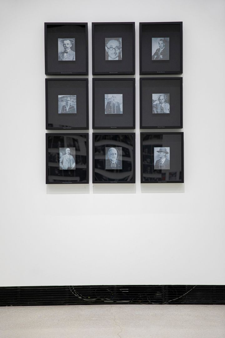 A series of 9 archival, black and white photographs of men are shown in black frames and arranged in a grid on a white gallery wall.