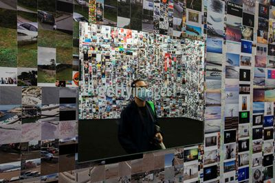 An installation of various images from the internet fill a wall in the gallery space.