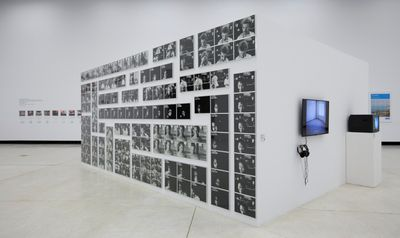 A series of black and white photographs, some featuring headshots, are arranged on a freestanding wall in the gallery space.