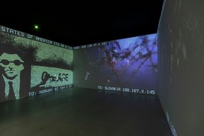 A three-channel video projection by DISNOVATION.ORG fills a small darkened room in the gallery space, showing pixelated imagery in green and blue hues.