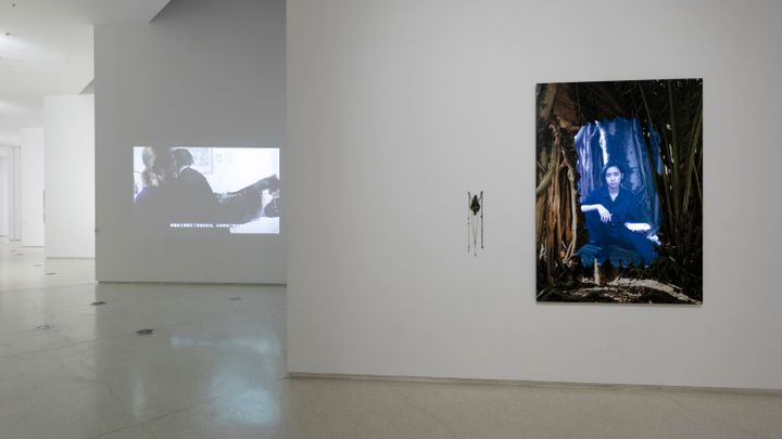 A portrait of a woman framed in imagery of branches is placed on the wall to the right. To the left, the gallery expands into another room.