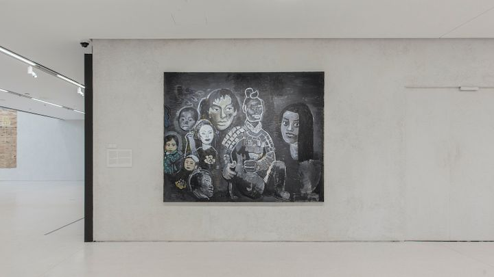 A painting by Yu Youhan with different figures outlined in white against a black background, hanging against a creme wall in the gallery space.