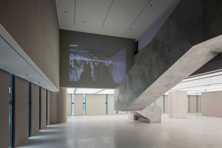 A video projection artwork by artist Xu Zhen, projected high near the ceiling against a concrete wall