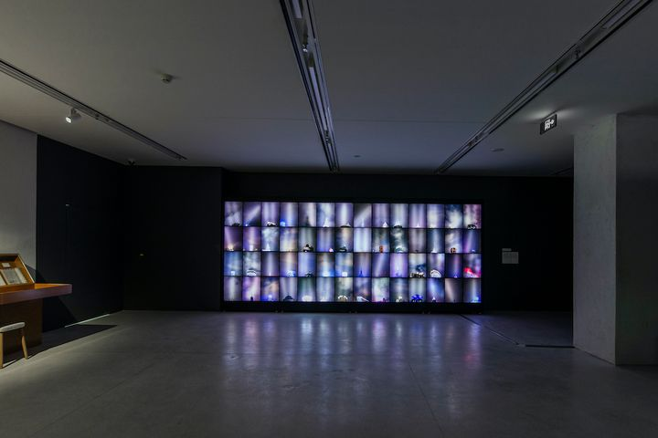 A Lightbox installation by Shi Yong features stacked screens in a darkened exhibition space.