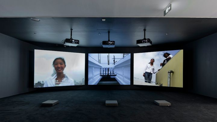 A three-channel video installation by Yang Fudong features one smiling woman on the far-left screen, and two women looking at the camera from above to the far-right.