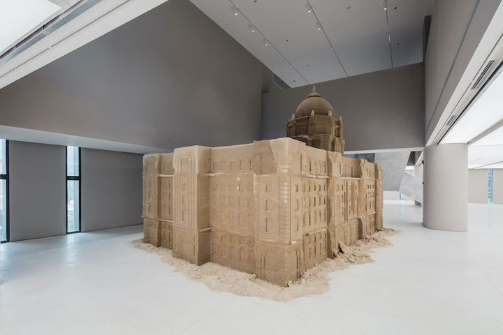 A bank building made of sand by Huang Yong Ping is assembled in the exhibition space. Some of the sand is crumbling to the floor.