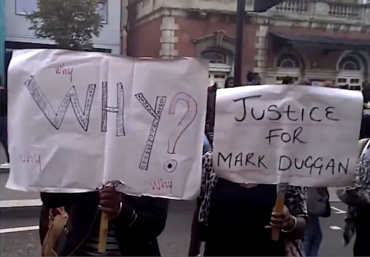 Image of protesters hold placards outside Tottenham Police Station