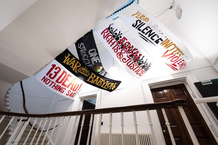 Artist Remee Bailey hanging artworks of Protest Signs from the ceiling in the exhition 'War Inna Babylon: The Community's Struggle for Truths and Rights'.