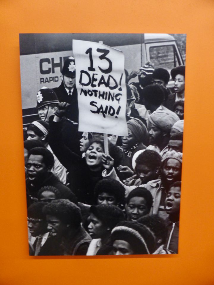 Portrait photo of people protesting with a man holding a sign saying '13 dead! Nothing said!'