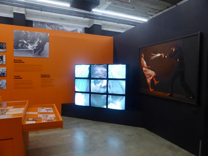 Installation shot of 9 video screens & wall text about the exhibition War Inna Babylon at Institute of Contemporary Art