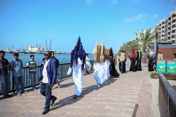 Meschac Gaba, Perruques Architectures Émirats Arabes Unis (2019). Processional performance. Performance view: Sharjah Biennial 14: Leaving the Echo Chamber (7 March–10 June 2019). Courtesy Sharjah Art Foundation.