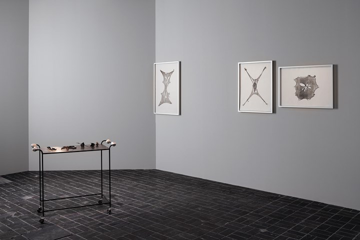 Julia Phillips, Operator I (with Blinder, Muter, Penetrator, Aborter) (2017). Partially salt-glazed ceramics, brass screws, stainless steel plate, metal wheel table; Expanded V (2016). Relief ink on paper; Expanded VI (2016). Relief ink on paper; Expanded IX, Quickly Fixed (2016). Relief ink on paper (left to right). From the series 'Expanded' (2013–2016). Exhibition view: We don't need another hero, 10th Berlin Biennale for Contemporary Art, KW Institute for Contemporary Art, Berlin (9 June–9 September 2018). Courtesy the artist. Photo: Timo Ohler.