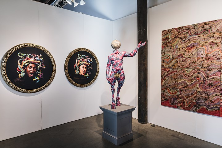 Yinka Shonibare, Medusa West (2015) and Medusa East (2015). Digital chromogenic print, bespoke wood frame. 114 cm diameter each; Pan (2018). Unique fibreglass sculpture, hand-painted with Dutch wax pattern, bespoke hand-coloured globe, gold leaf and steel baseplate. 143.8 x 84.8 x 59.7 cm; Elias Sime, Tightrope, non-essential speed (2017). 72.4 x 402.6 cm (left to right). Exhibition view: James Cohan Gallery, 1-54 Contemporary African Art Fair, New York (4–6 May 2018). Courtesy 1-54 Contemporary African Art Fair. Photo: © Katrina Sorrentino.