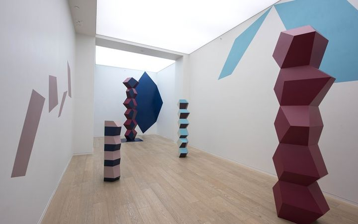 An installation shot of Simon Lee's gallery space with Angela Bulloch's blocky sculptures and colour block mural on the wall
